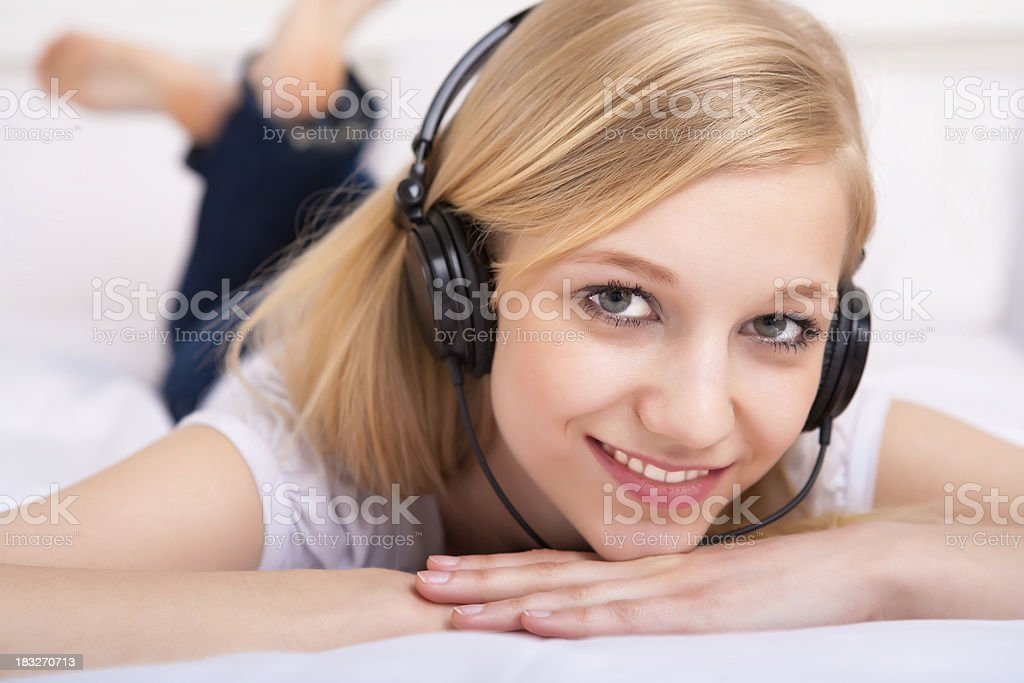 Young female listening to headphone in bed royalty-free stock photo