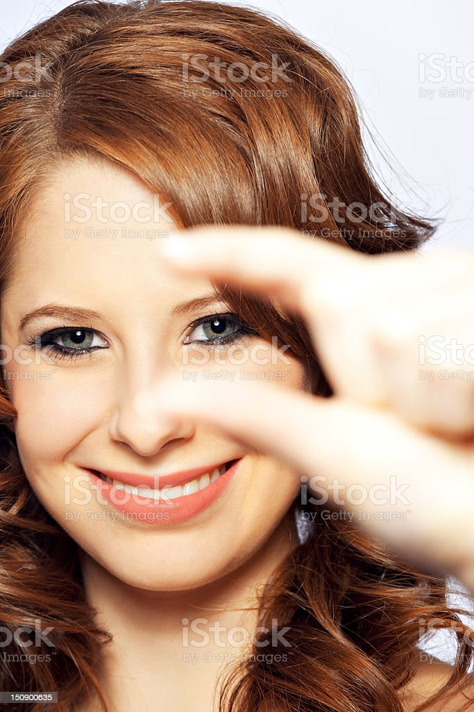 Young female looking through her fingers royalty-free stock photo