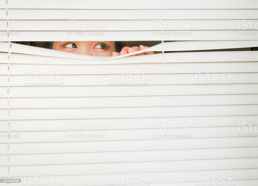 Young female looking Through Window Blinds. stock photo