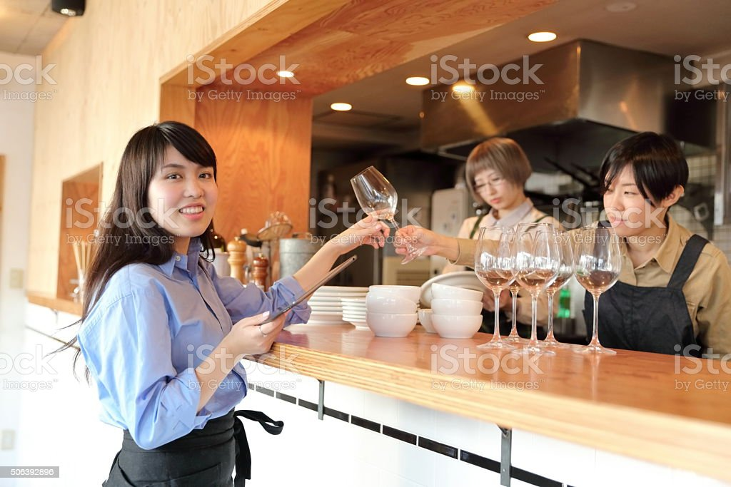 Young female manager receiving a glass from her staff stock photo