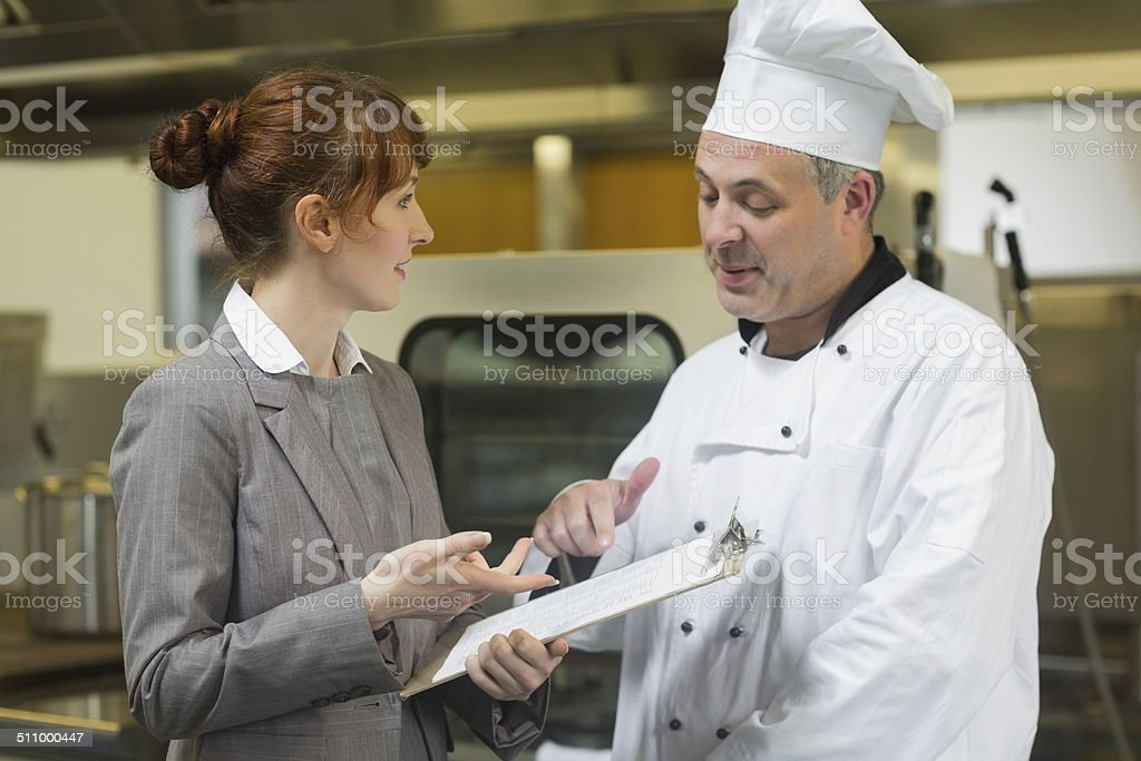 Young female manager talking to the head cook stock photo