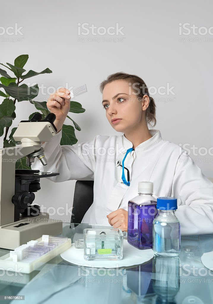 Young female microscopist selects a tissue sample stock photo