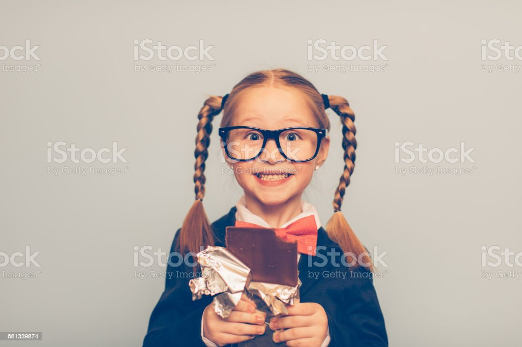 Young Female Nerd Eating a Chocolate Bar stock photo