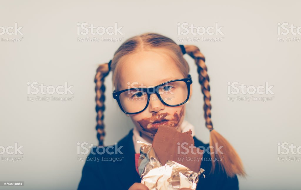 Young Female Nerd Eats Chocolate Bar stock photo