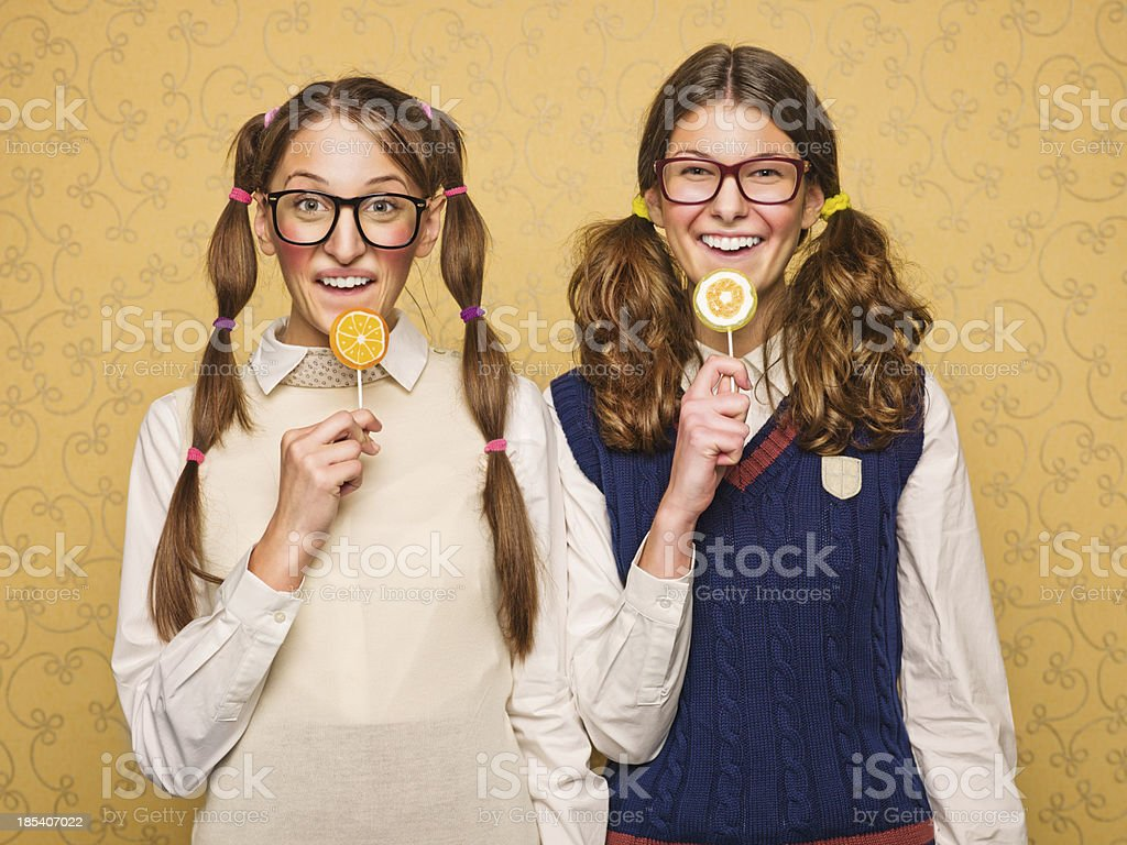Young female nerds with lollypops royalty-free stock photo