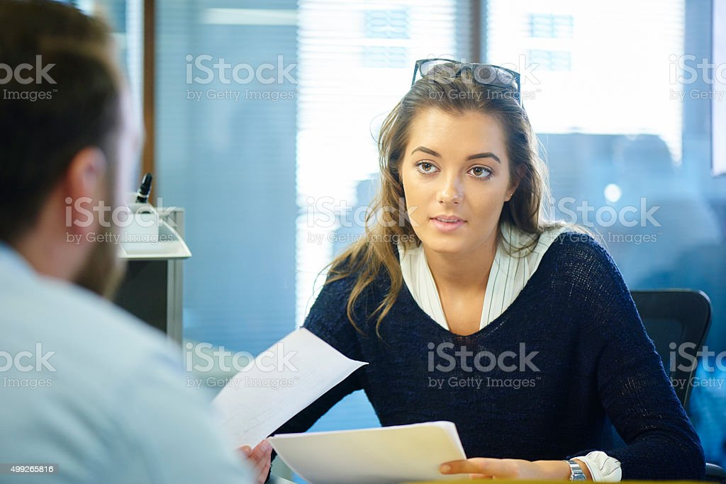 young female office worker chatting to a colleague stock photo