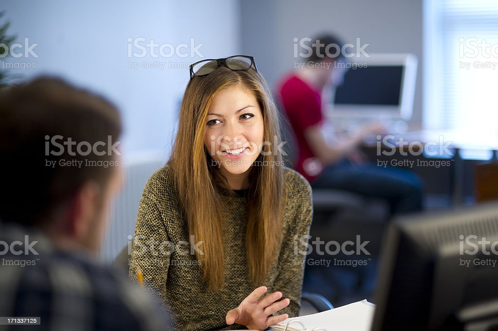 young female office worker chatting to colleague royalty-free stock photo