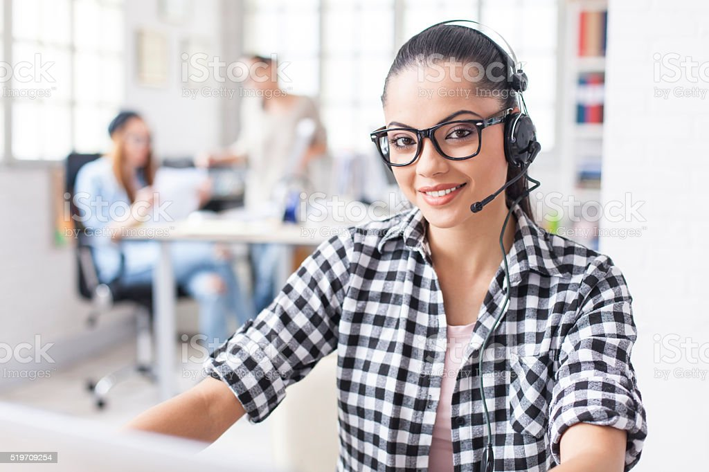 Young female office worker with headset stock photo