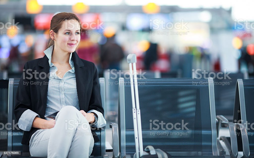 Young female passenger at the airport, using her tablet computer stock photo