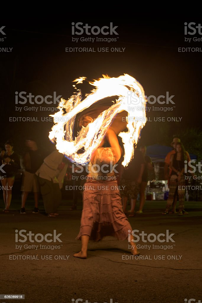 Young female performer spins fire at night stock photo