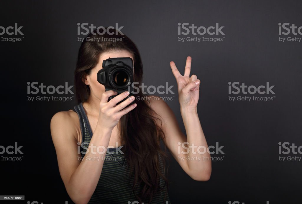 Young female photograph holding camera and makeing the photo and showing v-sign gesture on dark background with empty copy space. Closeup portrait stock photo