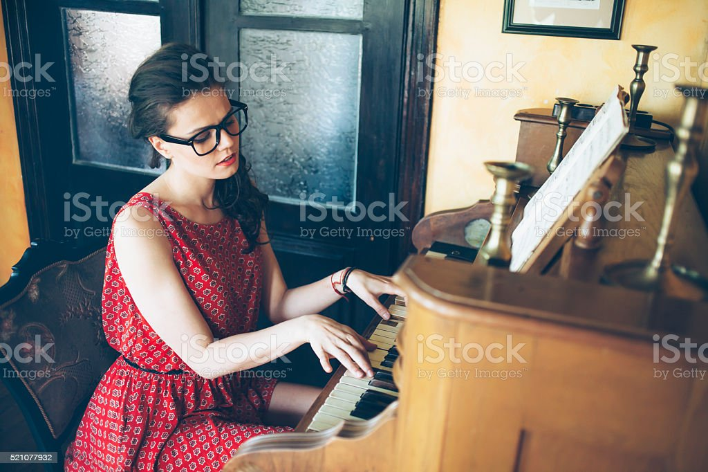 Young female pianist enjoying a piano practice stock photo