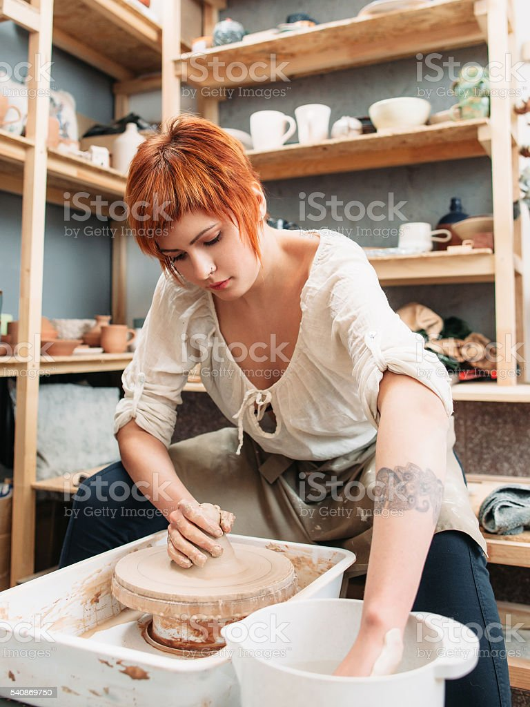 Young female potter working at studio stock photo