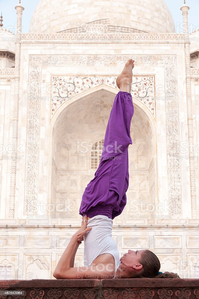 Young female practising yoga asana Sarvangasana at Taj Mahal stock photo