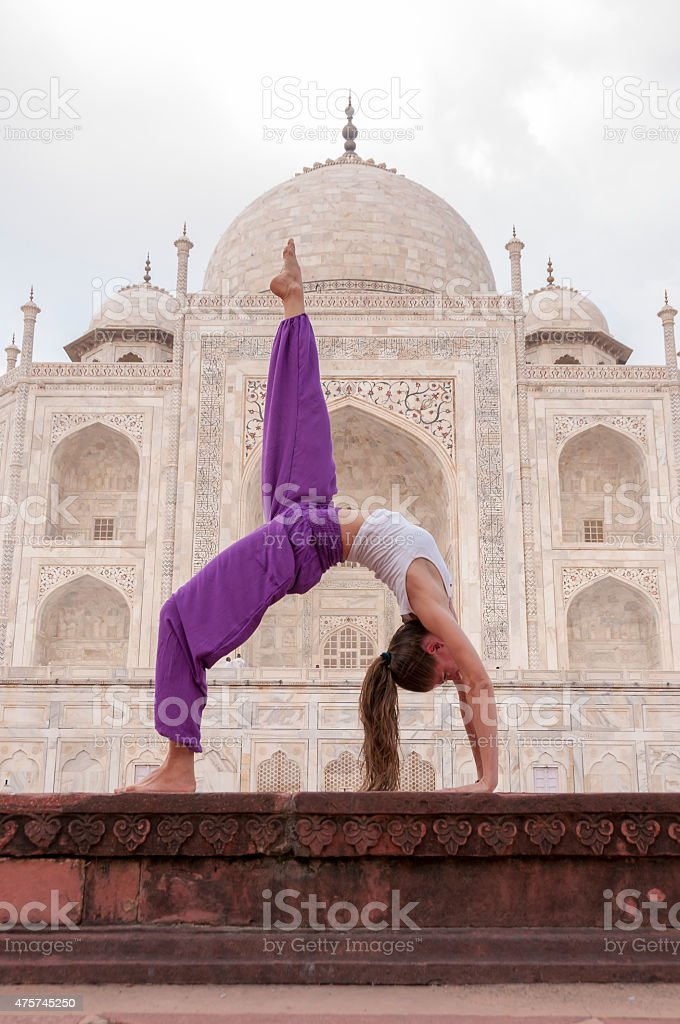 Young female practising yoga Bridge pose Eka Pada Setu Bandhasana stock photo