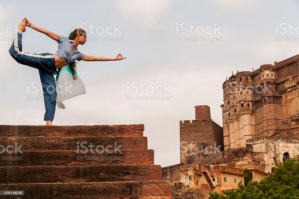 Young female practising yoga pose King Dancer or Natarajasana stock photo