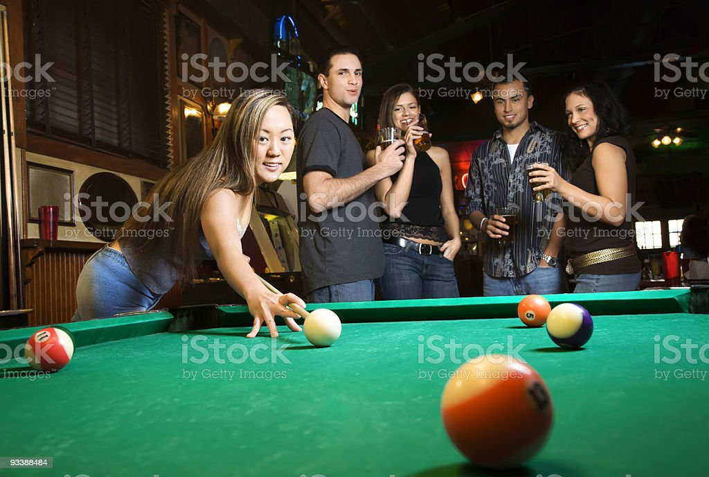 Young female preparing to hit pool ball. royalty-free stock photo