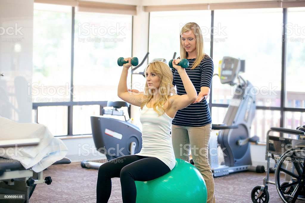 Young female PT working with a female patient stock photo