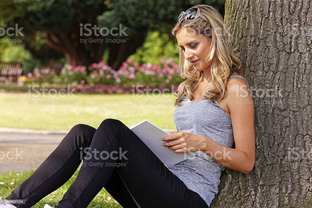 Young female reading a book in the park royalty-free stock photo