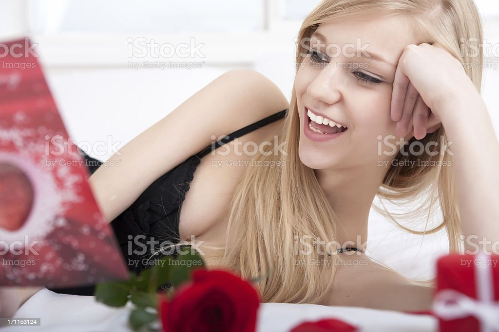 Young female reading valentine's card on bed royalty-free stock photo