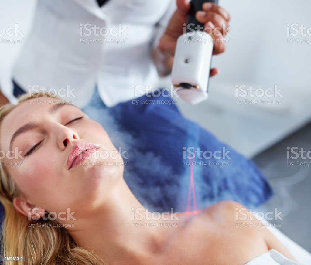 Young female receiving local cryotherapy treatment stock photo