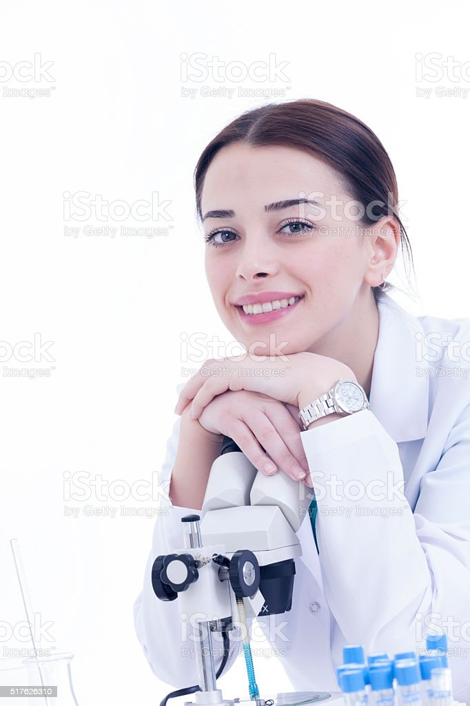 Young female researcher smiling with microscope on white background stock photo