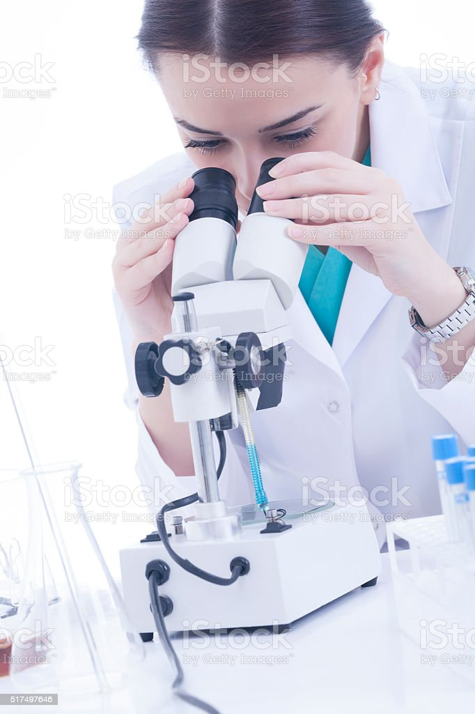Young female researcher using microscope on white background stock photo