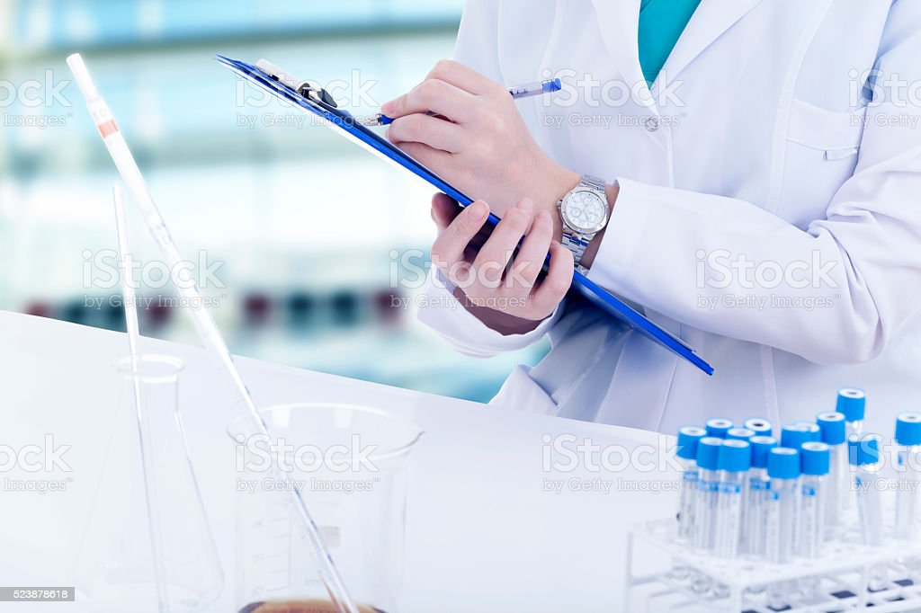 Young female researcher writing on research table stock photo
