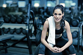 Young female resting on gym fitness equipment