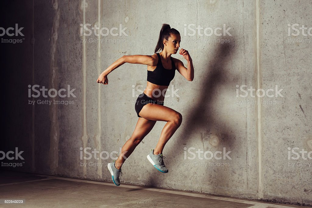 Young female runner running at concrete wall stock photo