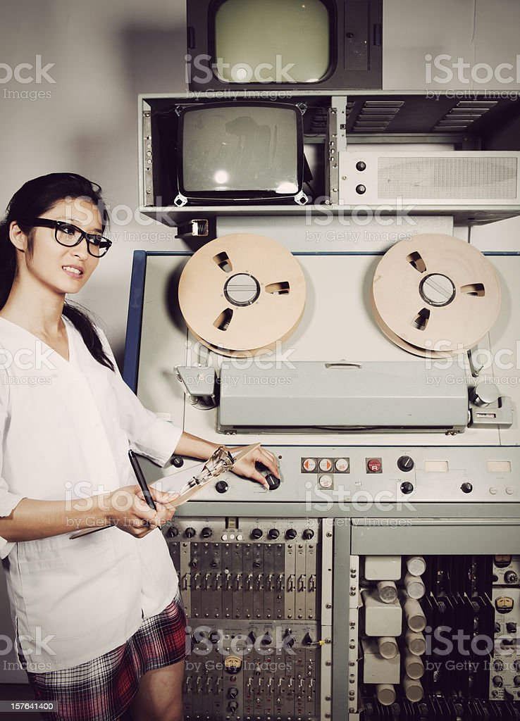 Young female scientist checking computer, 60s/70s vintage style stock photo