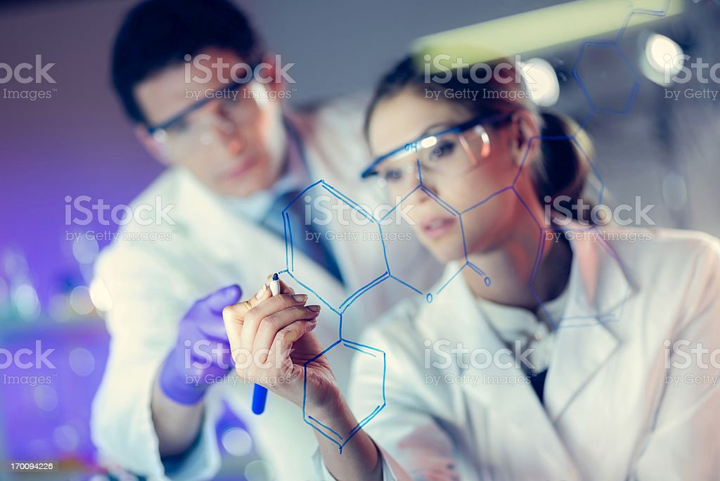 Young Female Scientist Drawing a Molecular Structure stock photo
