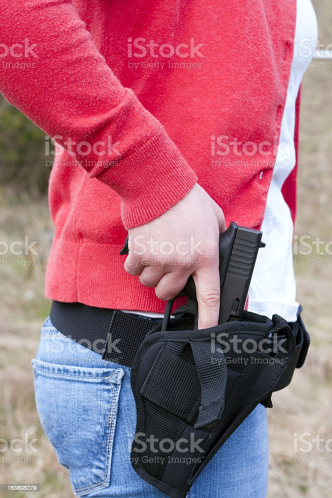 Young Female Shooter Drawing From Holster stock photo