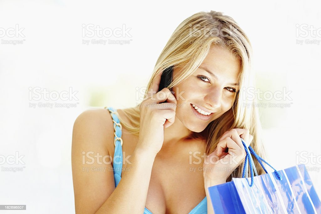 Young female shopper having a conversation on cellphone royalty-free stock photo