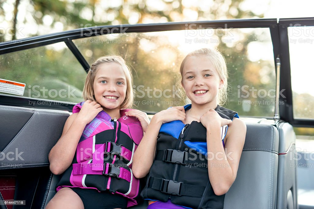 Young female siblings smile while wearing lifejackets stock photo