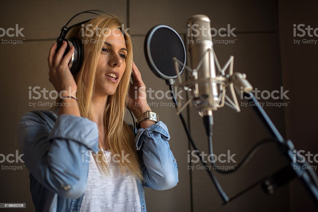 Young woman with headphones singing in music studio and recording a...
