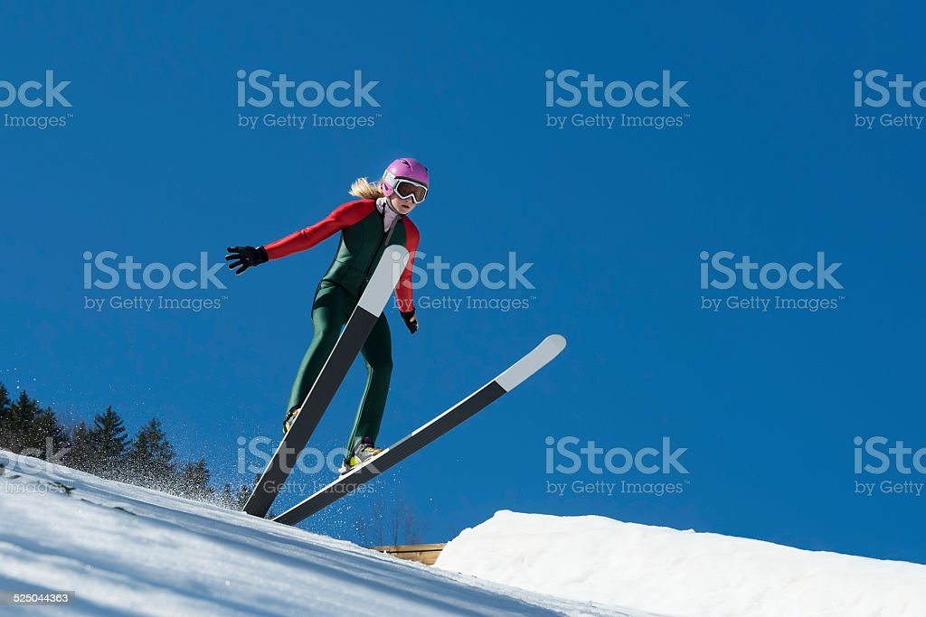 Young Female Ski Jumper Landing Against the Blue Sky stock photo
