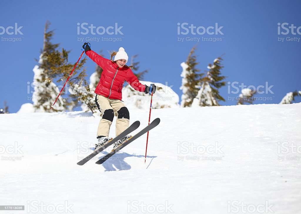 Young female skier jumping on mountain slope royalty-free stock photo