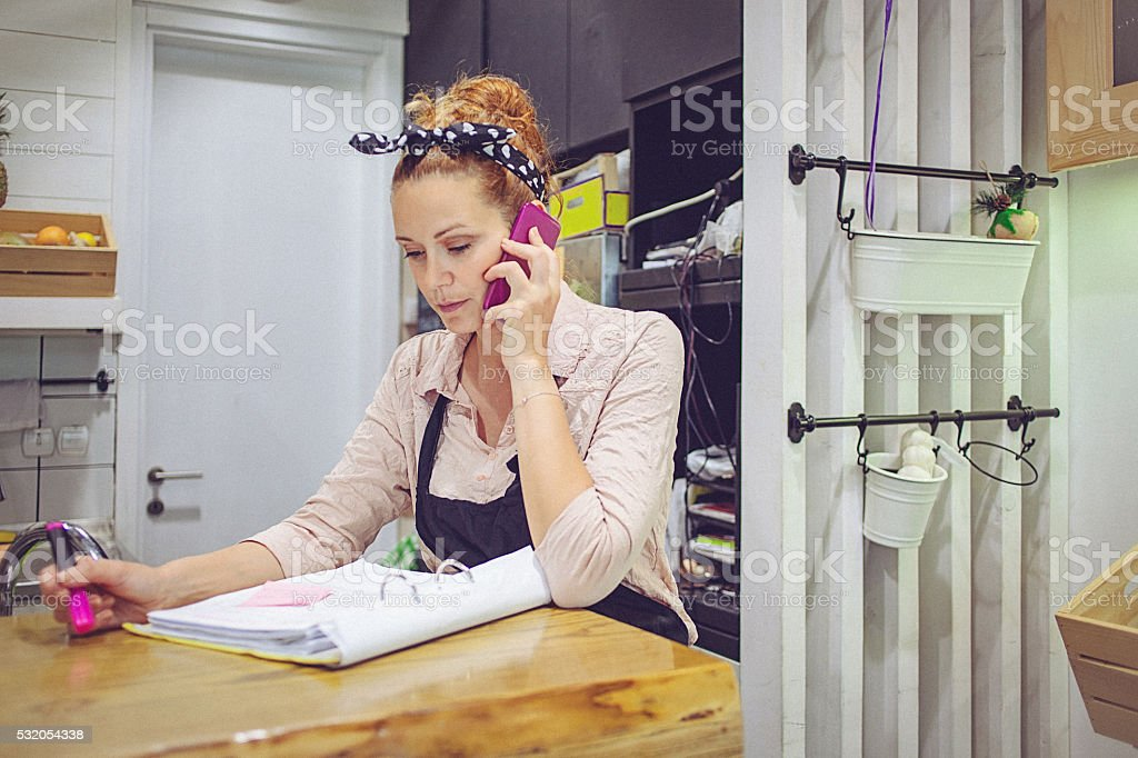 Young female small business owner doing the books at restaurant stock photo