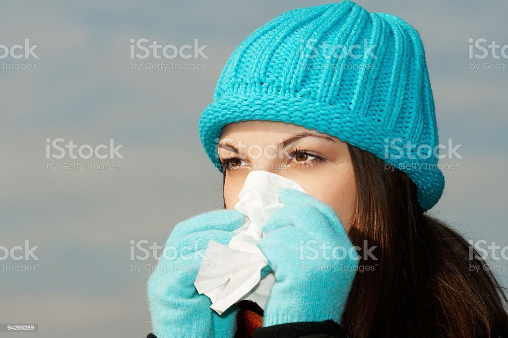 Young female sneezing into tissue royalty-free stock photo
