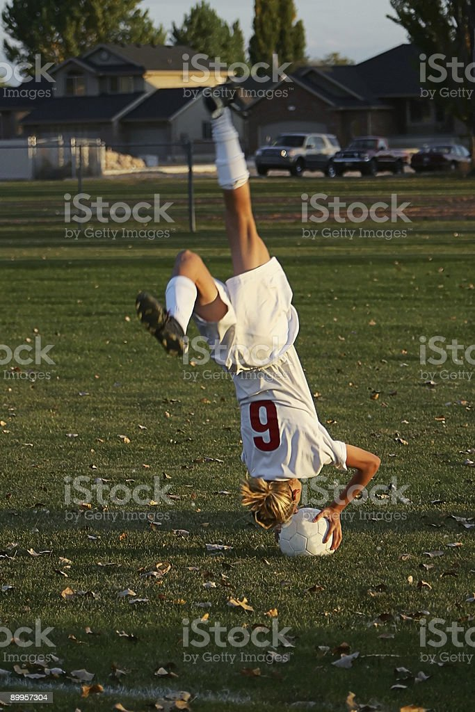 Young Female Soccer Player Executes Handsatand on Ball Throw In royalty-free stock photo