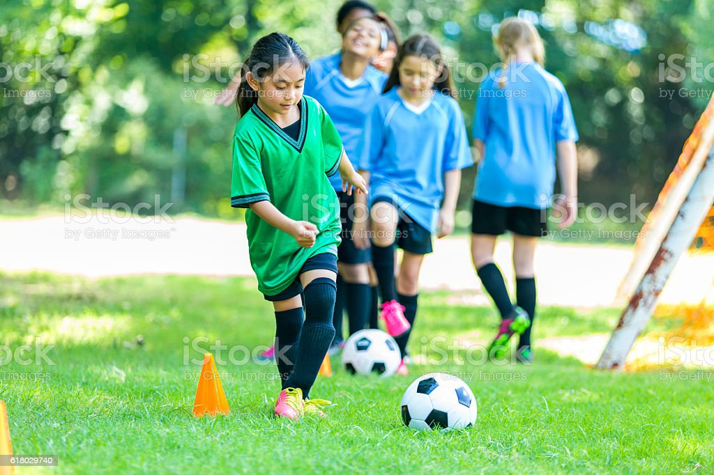 Young female soccer player practices drills stock photo