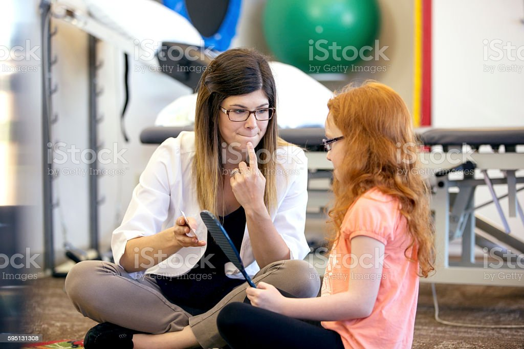 Young female speech therapist helping a young patient stock photo