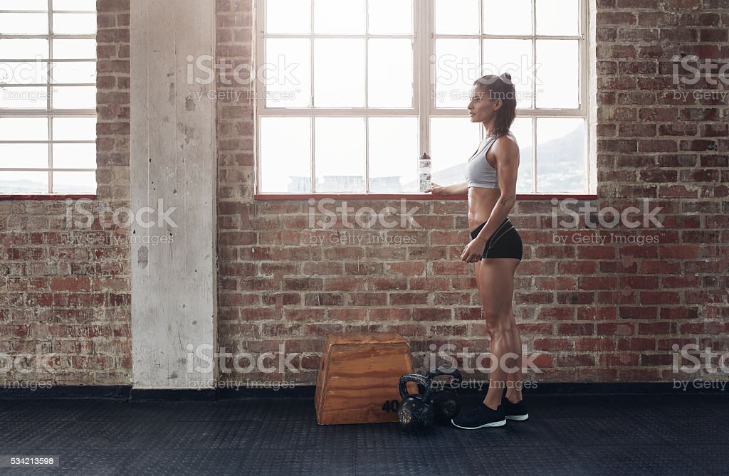 Young female standing at gym stock photo