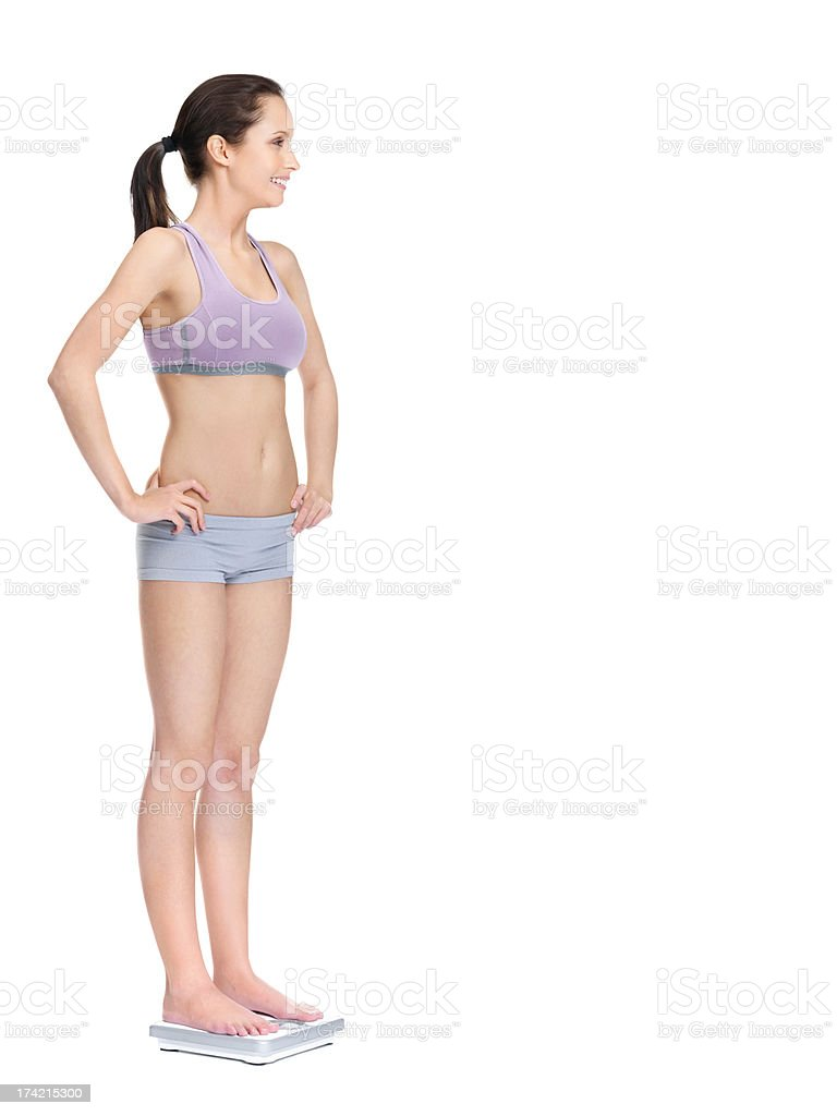 Young female standing on a weighing scale against white stock photo