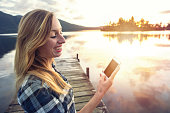 Young female standing on pier above lake text messaging