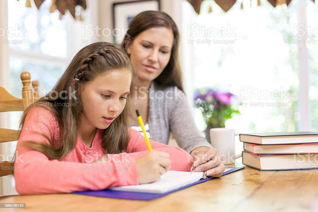 Young female student gets help on homework from mom stock photo