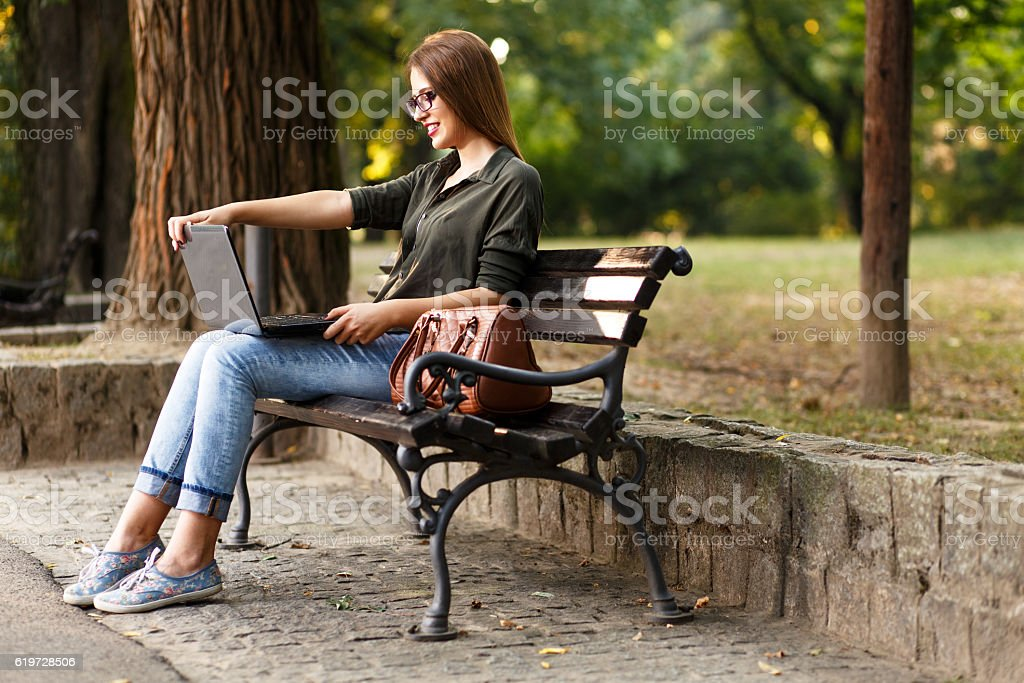 Young female student in park with laptop. stock photo