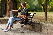 Young female student in park with laptop.