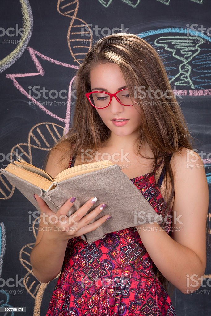Young female student reads book in front of school blackboard stock photo
